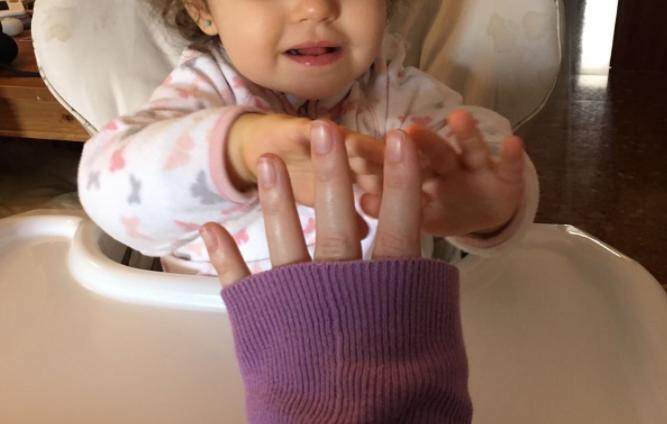La mano de una madre junto a las de su hija.