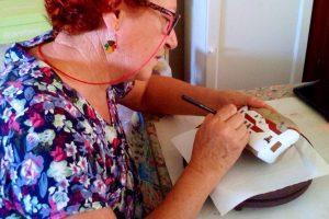 Natividad Ibáñez mientras pinta uno de los cantos en el salón de su casa./ Cedida