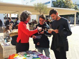 Susana Domínguez, presidenta de JereLesGay, informando a unos estudiantes en la mesa informativa ubicada en el Campus de Jerez, durante la semana del 'Sexo+Seguro'./ Cedida